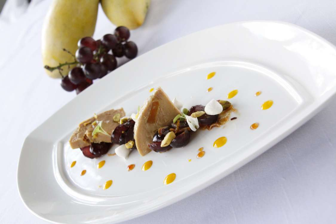 Mango foie gras terrine with black opal grapes and Thai flowers in tamarind sauce + crispy coconut + roasted pistachio